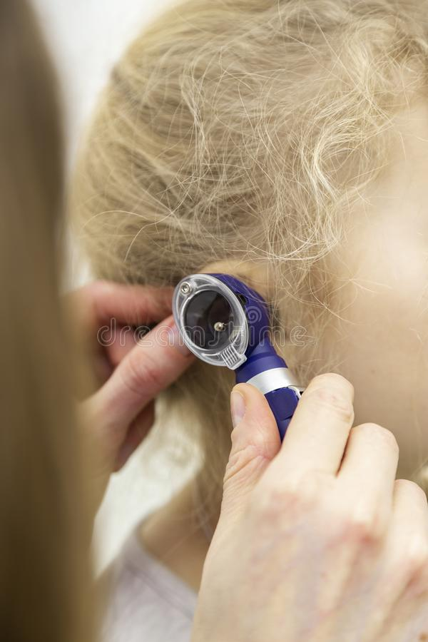 The doctor applies the otoscope to the ear. Hearing test with a special device stock images