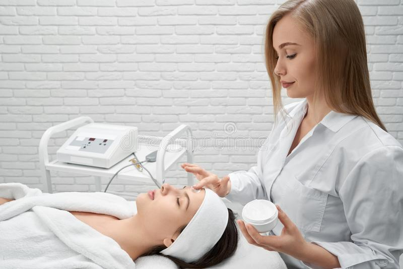 Doctor applying cream on face of young woman. stock photo