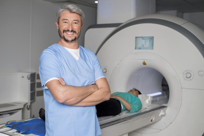 Doctor With Arms Crossed While Patient On CT Scan Machine royalty free stock image