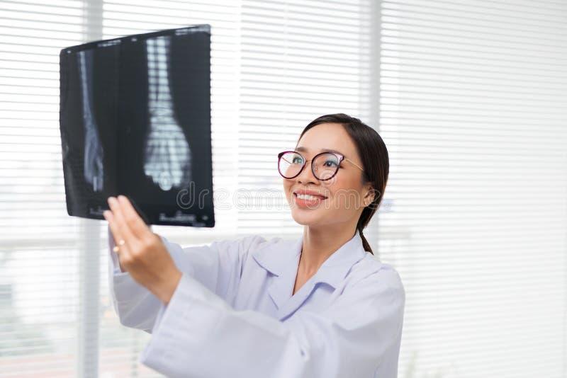 Doctor asiático de la mujer en el hospital que mira atención sanitaria de la película de radiografía imágenes de archivo libres de regalías