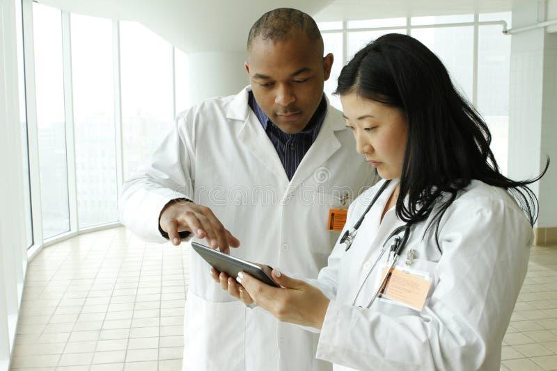 Doctor asiático de sexo femenino que habla con el doctor afroamericano con la tableta imágenes de archivo libres de regalías