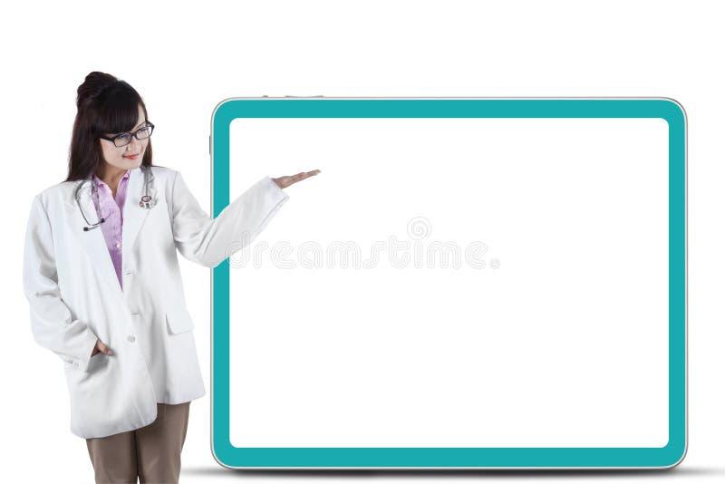 Doctor asiático de sexo femenino que presenta el copyspace foto de archivo