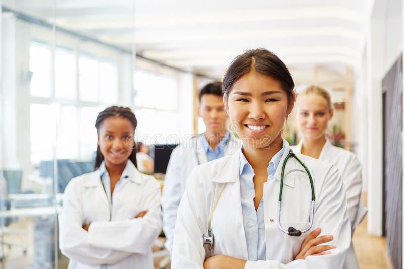 Doctor asiático joven con el personal hospitalario fotografía de archivo libre de regalías