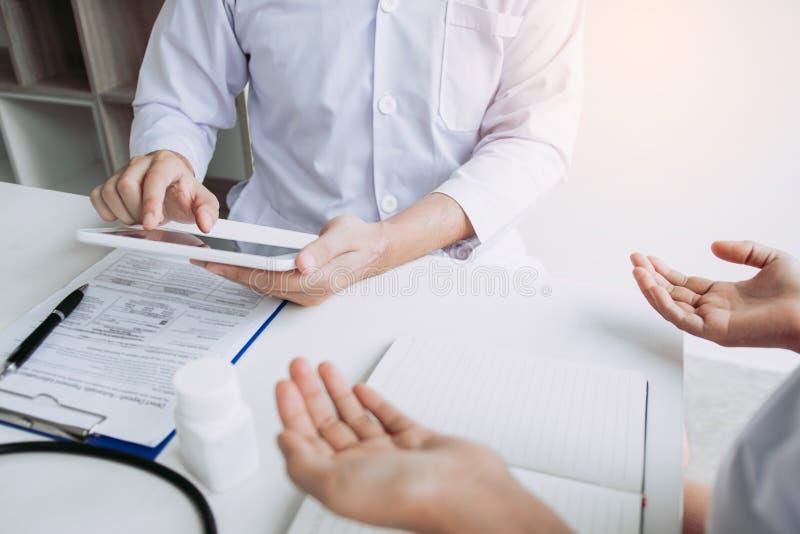 Doctor asiático que habla al paciente en la clínica mientras que usando la tableta que explica la condición paciente y el resulta fotografía de archivo