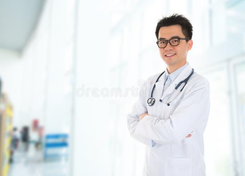 Doctor asiático que se coloca en el pasillo del hospital imagen de archivo