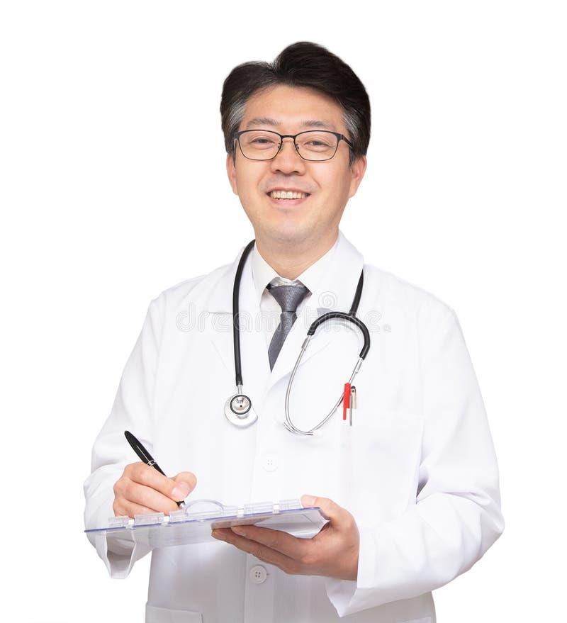Doctor asiático que sonríe y que escribe una carta Aislado en el fondo blanco imagen de archivo
