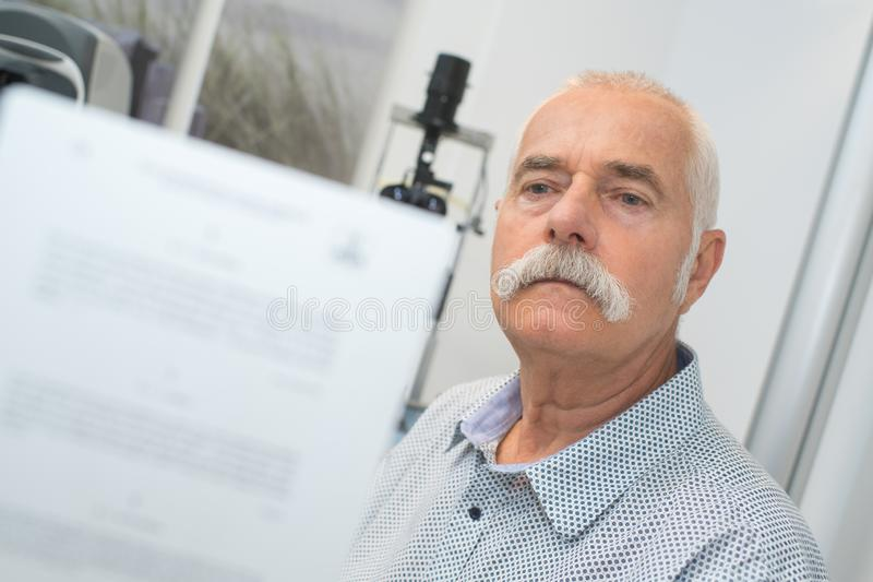 Doctor asking patient to read chart behind him. Man stock images