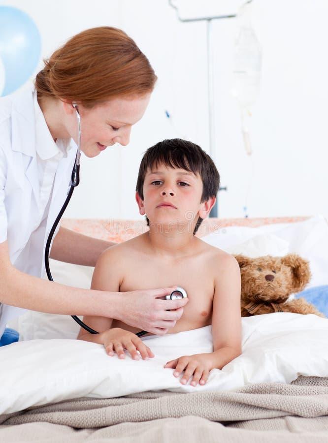 Doctor atento que examina a un niño pequeño fotos de archivo
