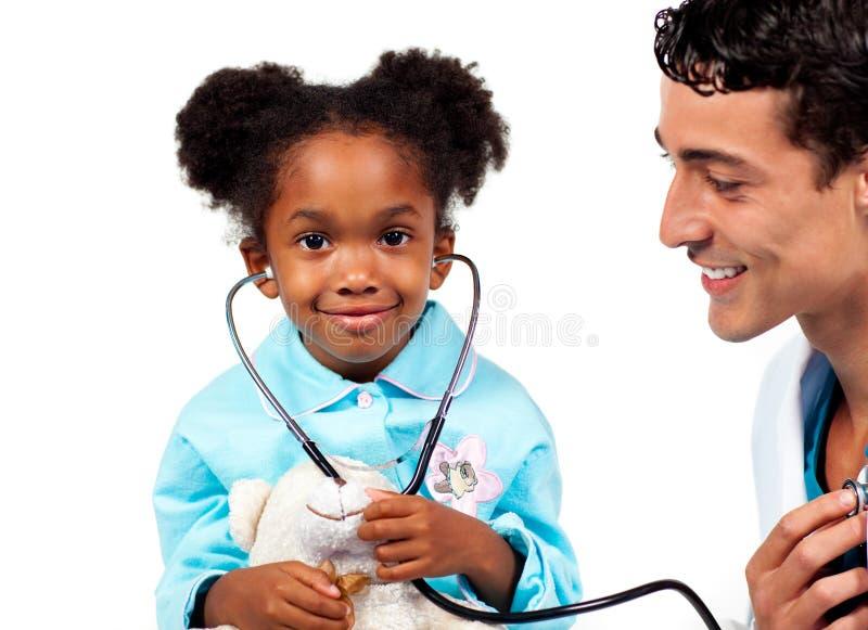 Doctor atento que juega con su paciente foto de archivo