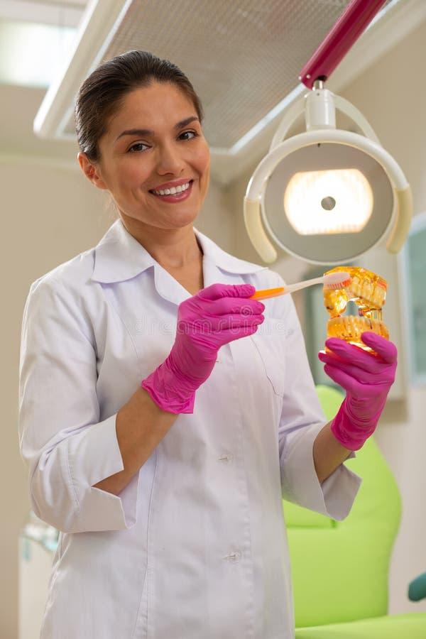 Doctor atractivo de la mujer que se coloca delante de una silla de los dentistas imagenes de archivo