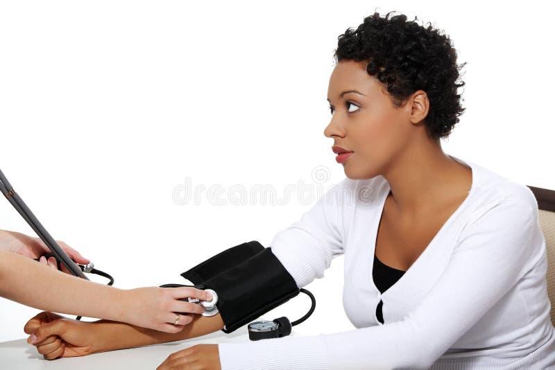 Doctor att kontrollera blodtryck av gravid kvinna. arkivbild