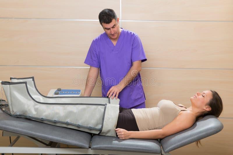 Doctor att kontrollera lägger benen på ryggen pressotherapy bearbetar med maskin på kvinna fotografering för bildbyråer