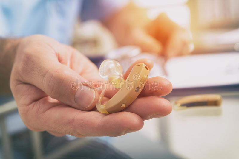 Doctor holding hearing aid stock images