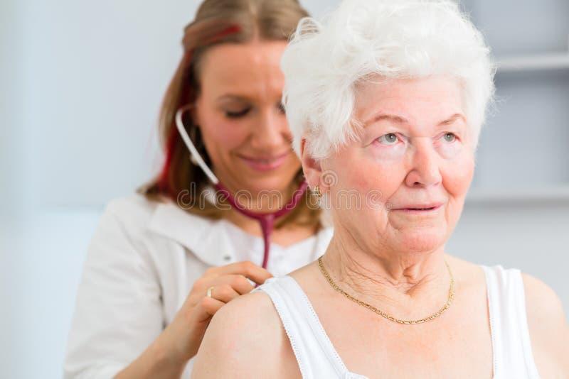 Doctor auscultating el paciente mayor en la práctica fotografía de archivo libre de regalías