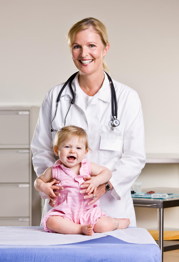 Doctor and baby girl in doctor office stock photo