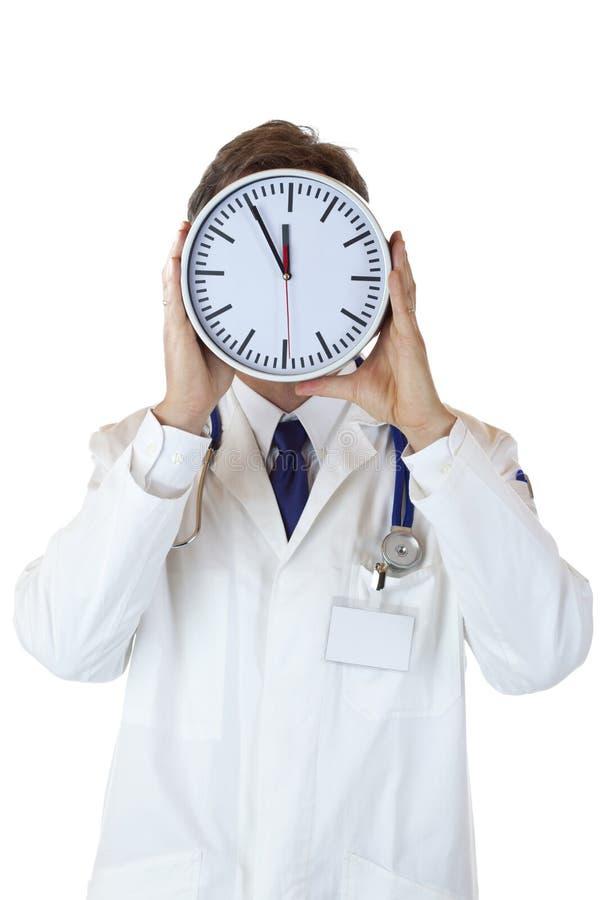 Doctor bajo presión de tiempo detrás de la cara de reloj imagenes de archivo