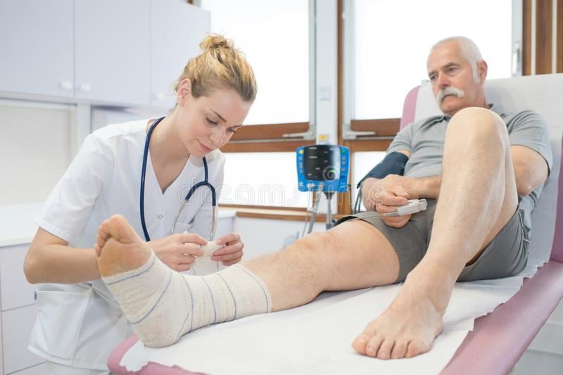 Doctor bandaging seniors patients leg in hospital royalty free stock photography