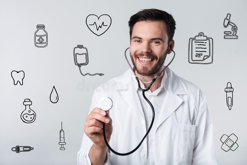 Doctor barbudo positivo que sonríe y que sostiene su estetoscopio imagen de archivo