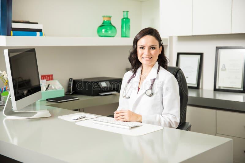 Doctor bastante de sexo femenino en su oficina imagen de archivo