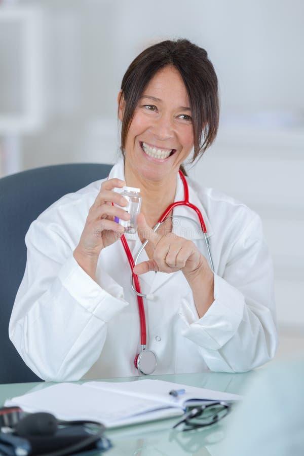 Doctor bastante de sexo femenino que muestra píldoras al paciente foto de archivo libre de regalías
