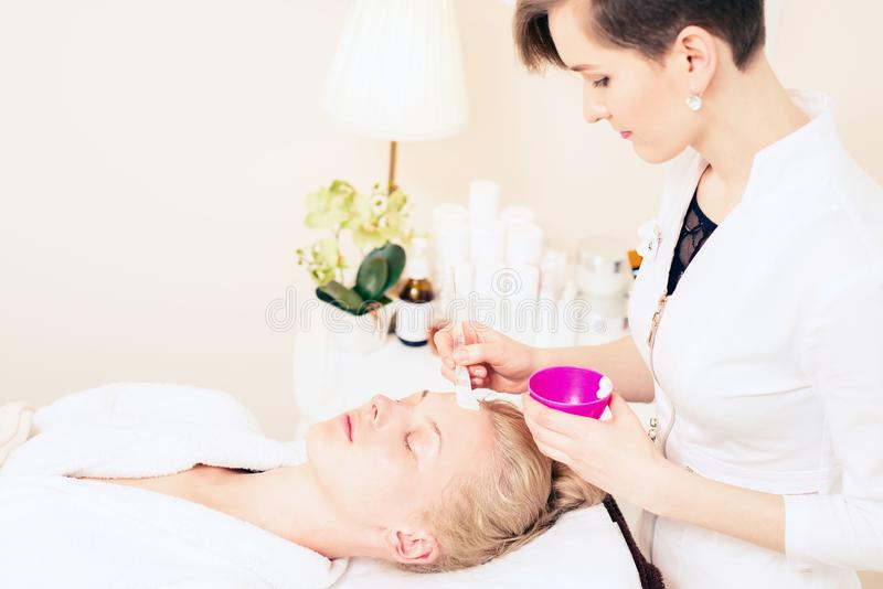 The doctor beautician applies the cream to the patient`s face with a little dog. young girl caring for skin in the spa salon. stock photos