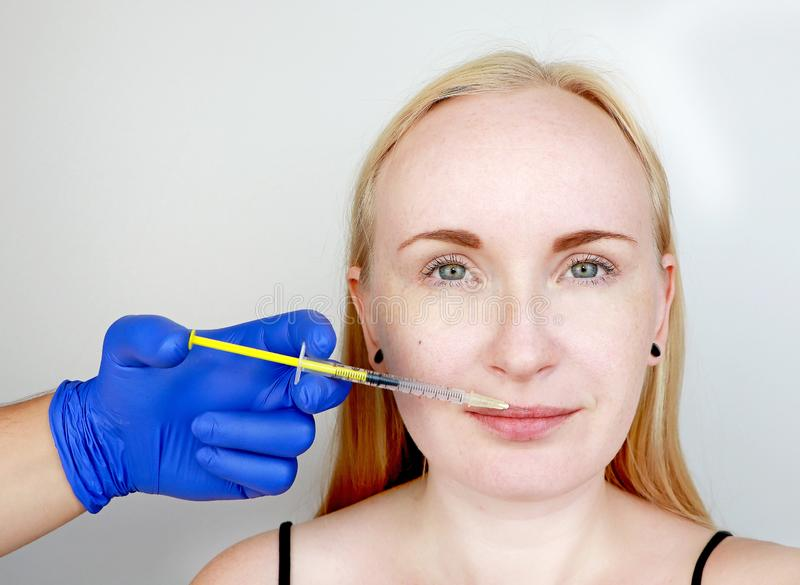 The doctor beautician conducts contour plastic lips: an injection into the lips, lip augmentation. Hyaluronic Acid Injection stock photography