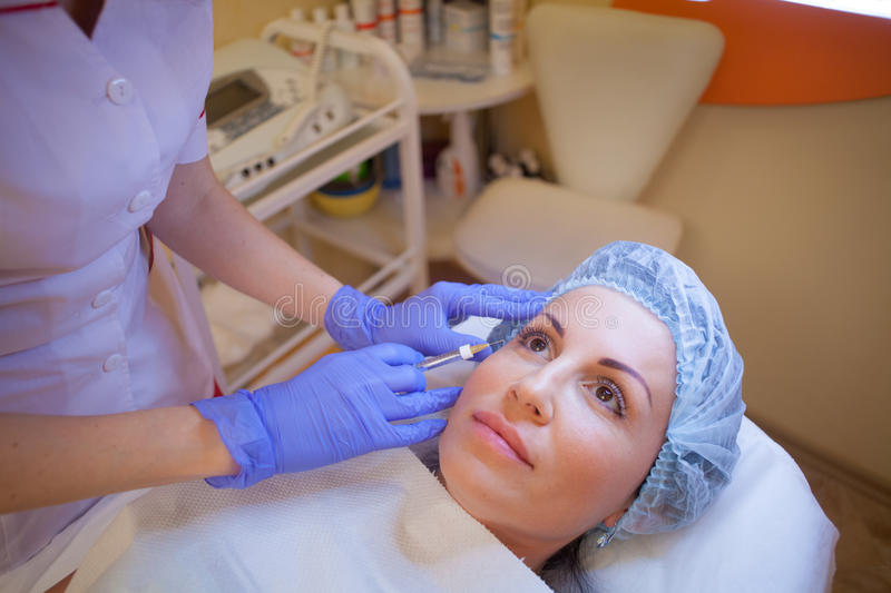 Doctor beautician increases lip patient an injection syringe royalty free stock photo