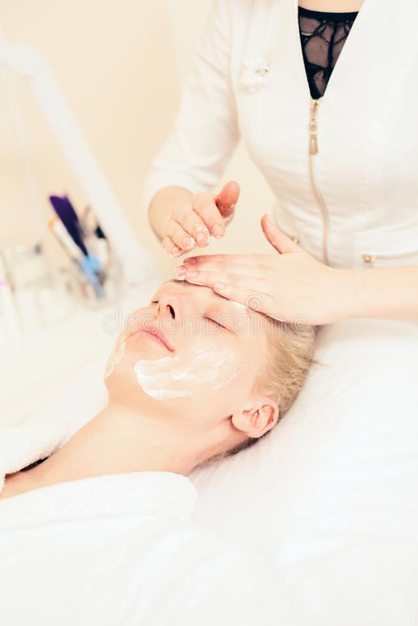The doctor beautician puts the cream on the face of the patient. spa cosmetology. healthy lifestyle concept.  stock images