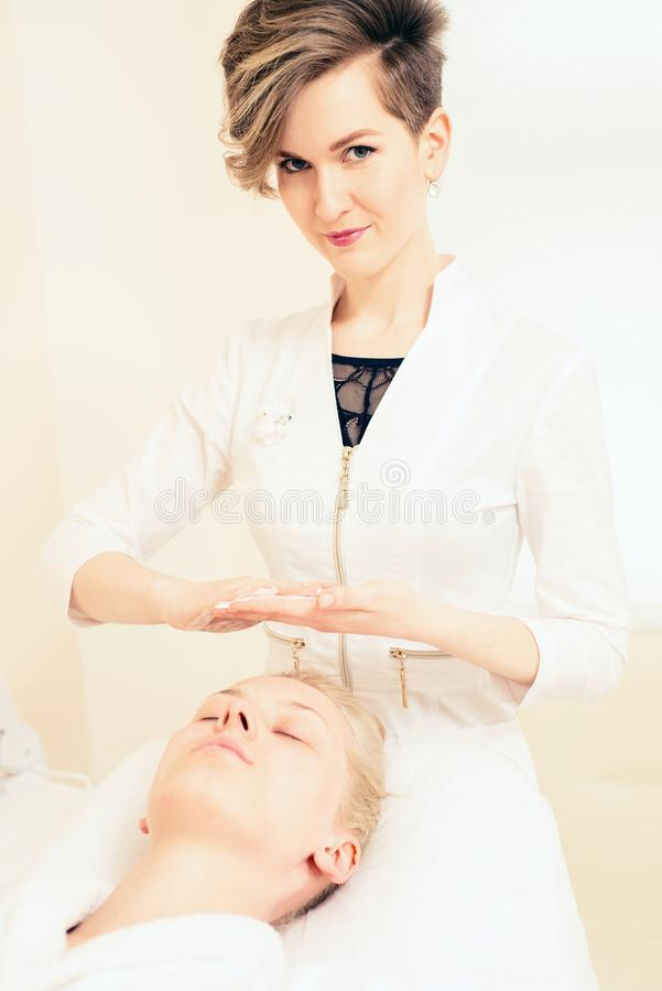 The doctor beautician puts the cream on the face of the patient. spa cosmetology. healthy lifestyle concept.  stock photo