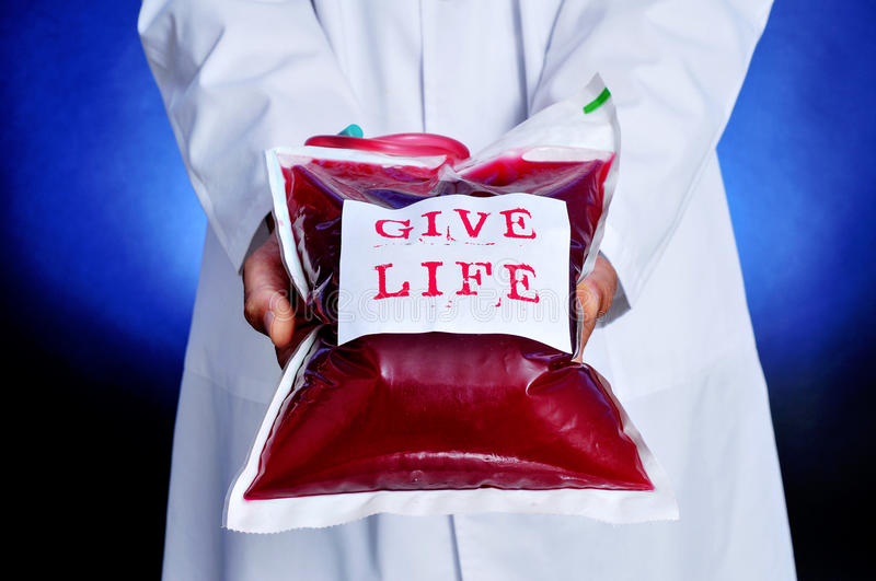 Doctor with a blood bag with the text give life royalty free stock photography