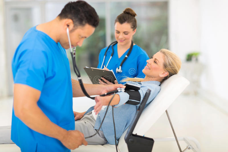 Doctor blood pressure. Caring medical doctor taking mid age woman's blood pressure stock photos