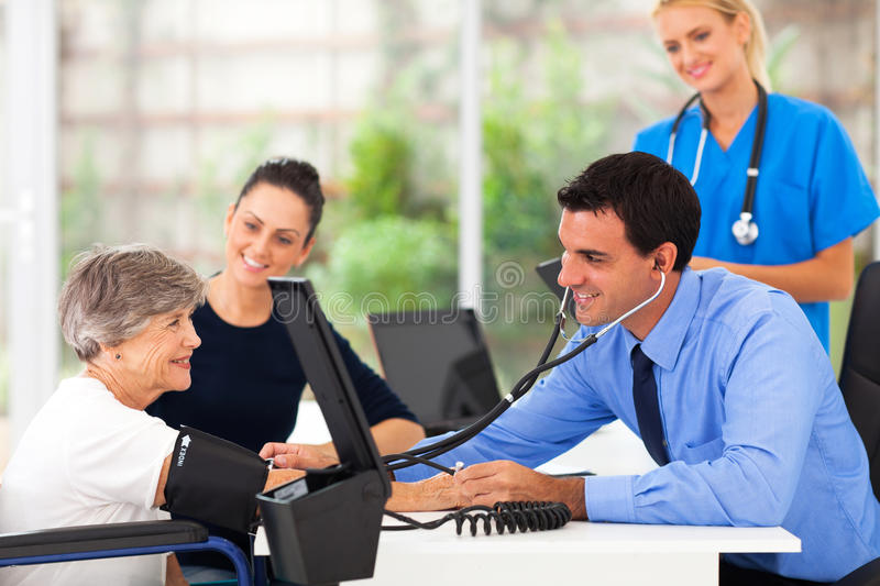 Doctor blood pressure. Friendly medical doctor taking senior woman's blood pressure stock photos