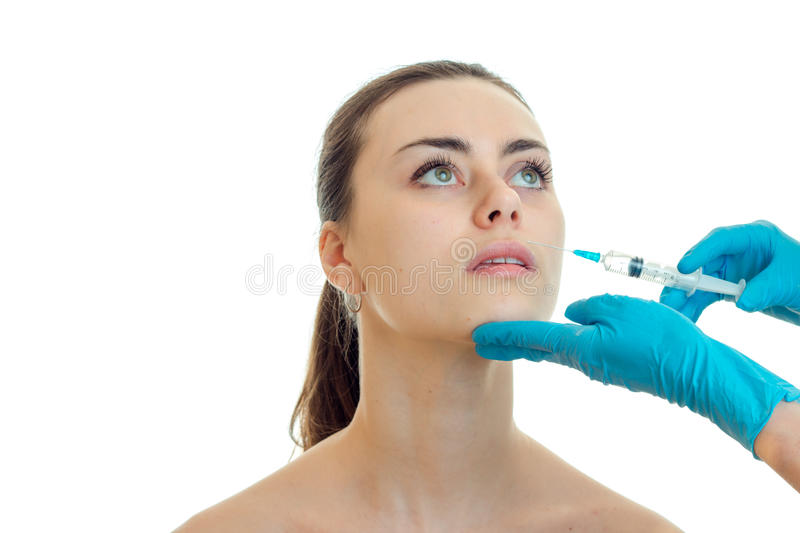 Doctor in blue gloves makes an analgesic syringe injection on the face of the girl isolated on a white background royalty free stock photos
