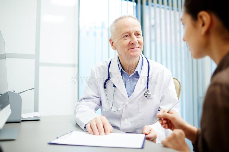 Doctor bueno de comprensión que habla con el paciente imágenes de archivo libres de regalías