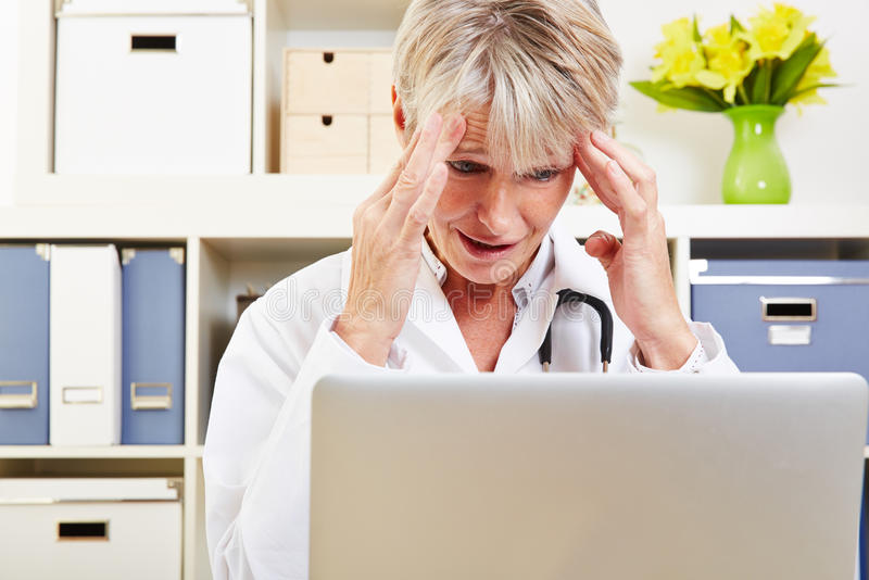 Doctor with burnout in office. Elderly female doctor with burnout syndrome in her office at the desk royalty free stock image