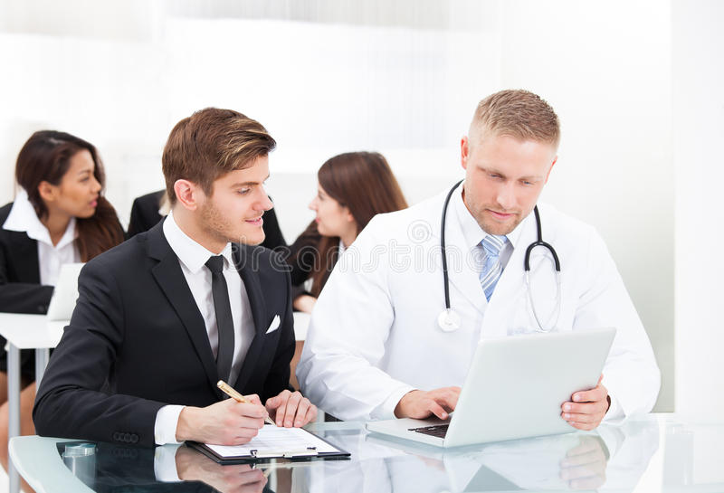 Doctor And Businessman Discussing Over Laptop royalty free stock image
