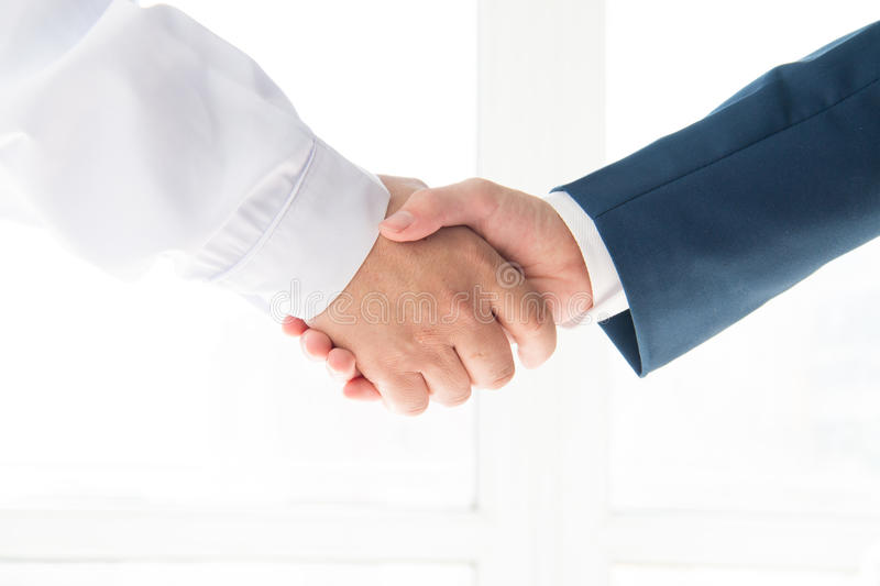 Doctor and businessman. Shaking hands stock photos