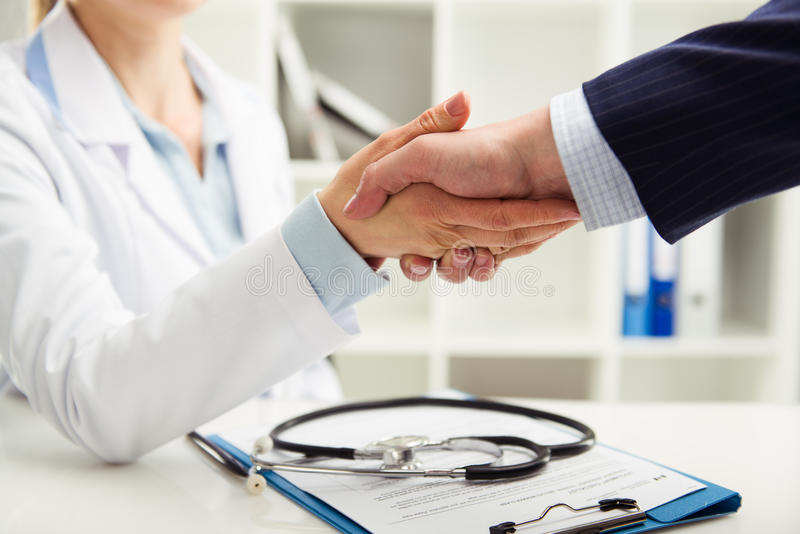 Doctor and businessman. Woman doctor shaking hand with businessman in the office. Young medical specialist in uniform meeting partner for discussion. Shallow stock photo