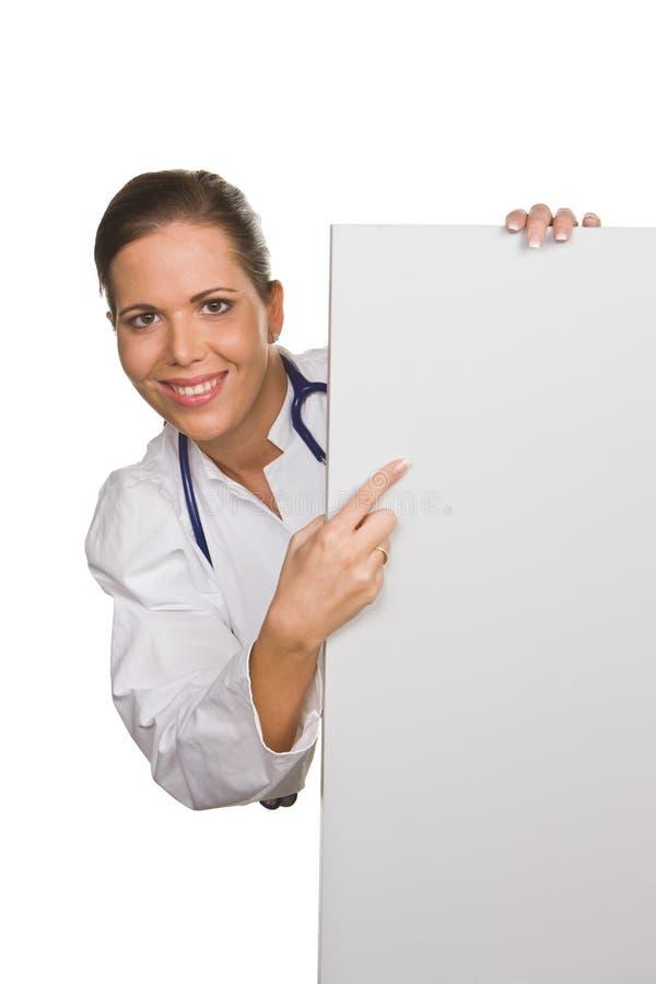Doctor cómodo joven con un cartel blanco vacío imagen de archivo libre de regalías