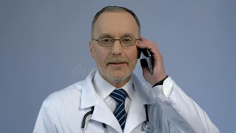 Doctor calling patient, medical consultation service by phone, health care stock photography