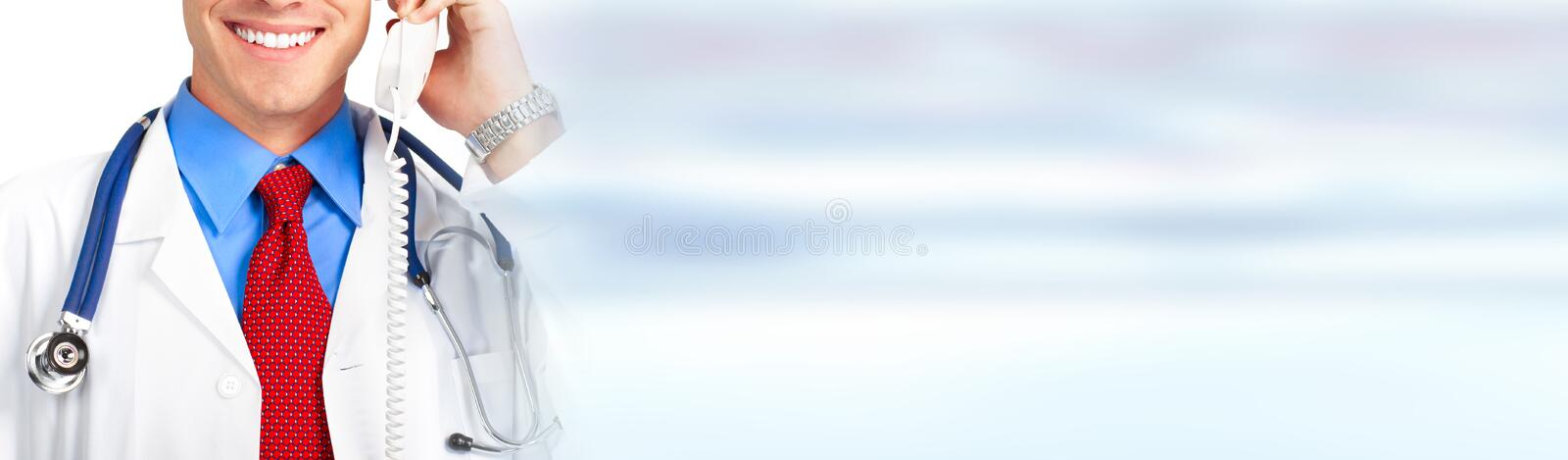 Doctor calling by phone. Young smiling doctor with phone on blue medical clinic background royalty free stock photos