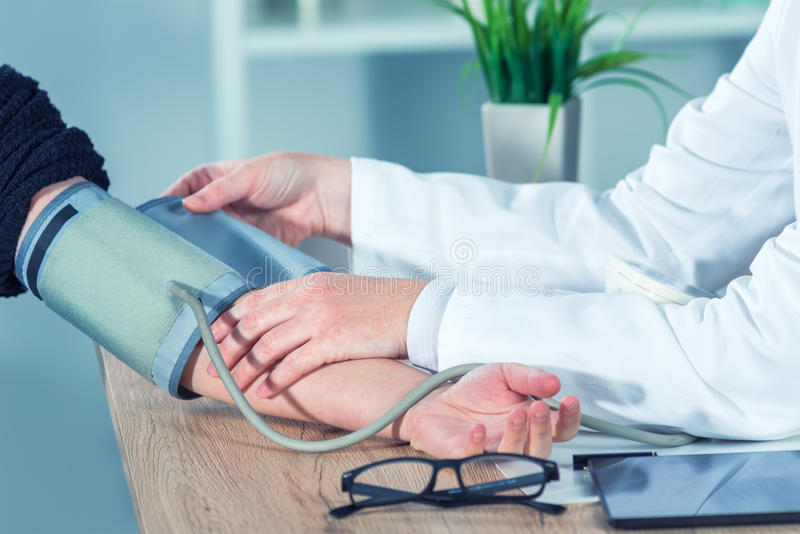 Doctor cardiologist measuring blood pressure of female patient stock photography