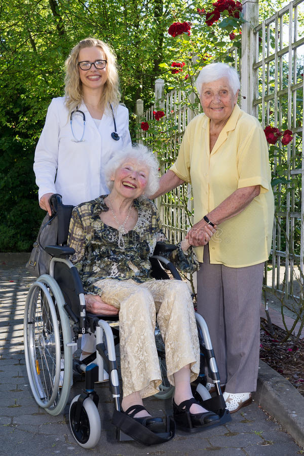 Doctor, Caregiver and Elderly Smiling at Camera stock photo