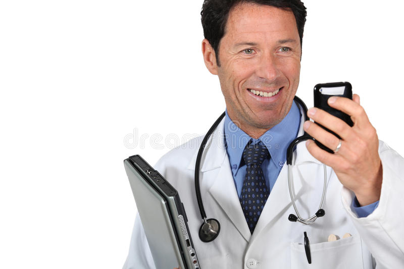 Doctor with a cellphone. And laptop computer royalty free stock images