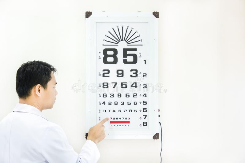 Doctor check patient eye problem by snellen chart. And white background stock image
