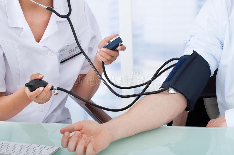 Doctor checking blood pressure of businessman. Cropped image of young female doctor checking blood pressure of businessman in clinic stock photo