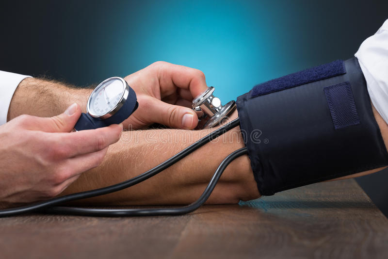Doctor Checking Blood Pressure Of Patient At Table royalty free stock photography