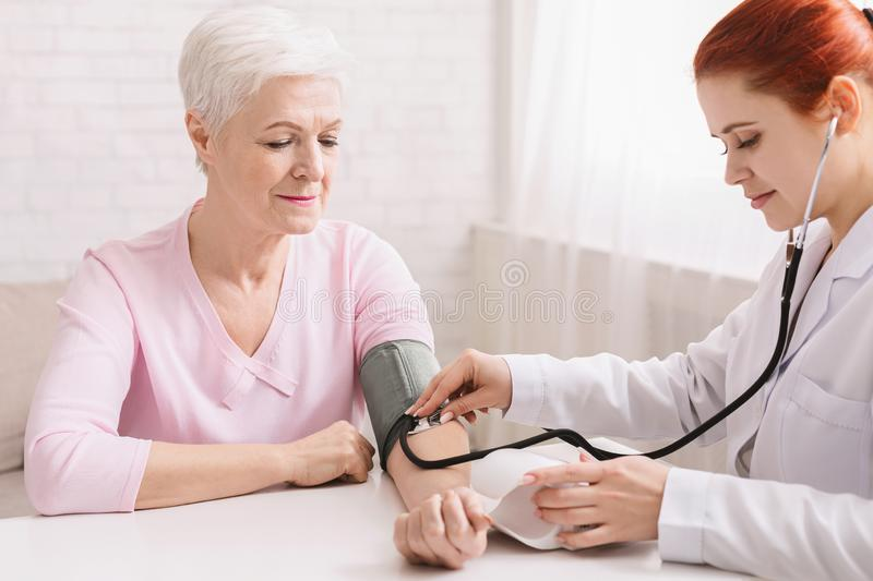 Doctor checking blood pressure of senior patient royalty free stock image
