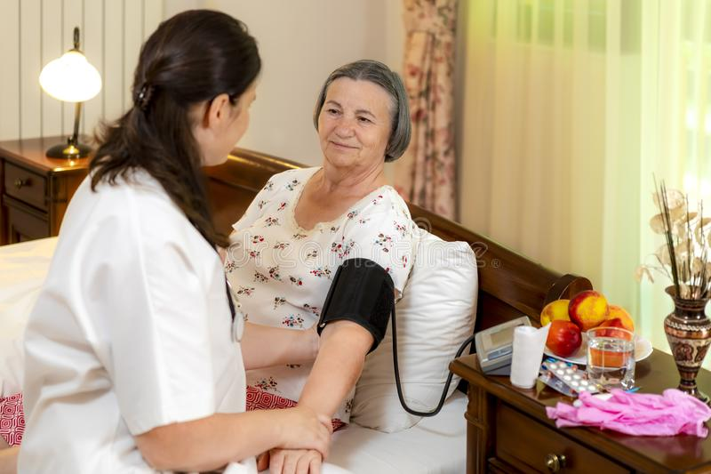 Doctor checking blood pressure to senior woman stock photo