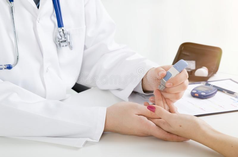 Doctor checking blood sugar level. Doctor patient diabetes lancet glucometer blood glucose office concept royalty free stock images
